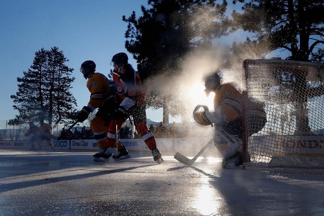 Zwei Eishockeyspieler vor einem Torwart, im Hintergrund Bäume